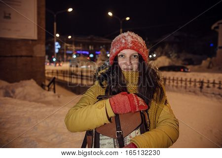 the girl's portrait against the background of the evening city which to something is surprised and holds in the winter a backpack in hand. in the light of city lamps.