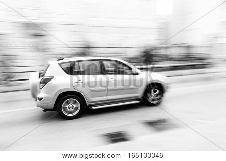 Fast Moving Car On The City Roadway In Motion Blur. Black And White Image.