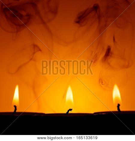Three candle smoke against a dark background warm