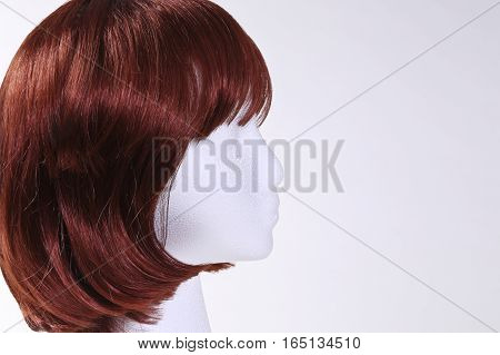 Female mannequin wearing red wig with copy space