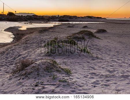 Natural sand berm creates levee for estuary water shoreline.