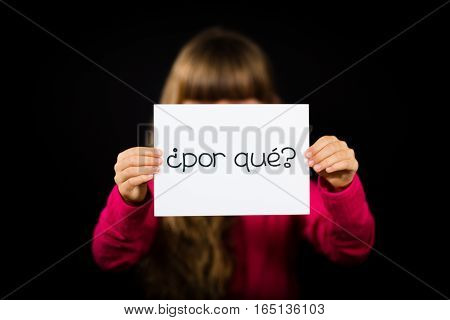 Studio shot of child holding a sign with Spanish words Por Que - Why