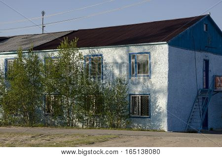Blue misery and poor two-storeyed building with trees around