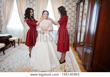 Two Young And Gorgeous Bridesmaids On Red Dress Wear Bride On Her Room At Wedding Day.