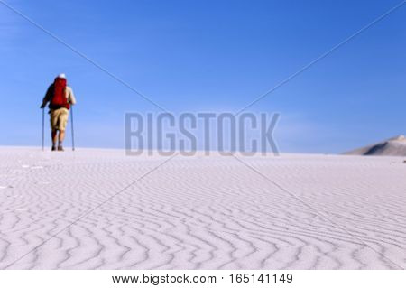 The journey in the desert dunes with white on a backpack.