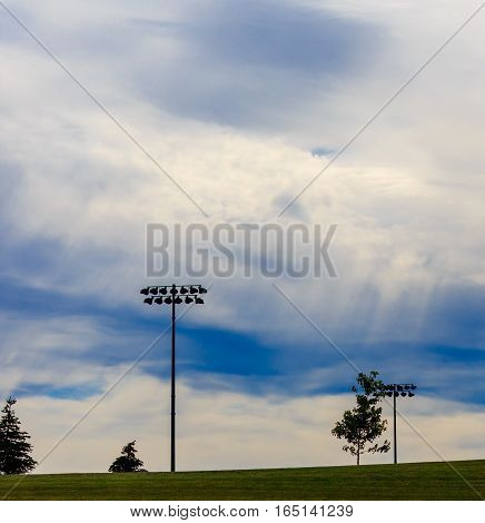 Stadium lights with blue and white sky and rays of sunshine.