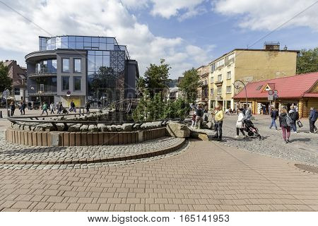 ZAKOPANE POLAND - SEPTEMBER 23 2016: Several people walk at the street Krupowki that is a frequently visited place by tourists coming to town. Many tourist attractions are located there.