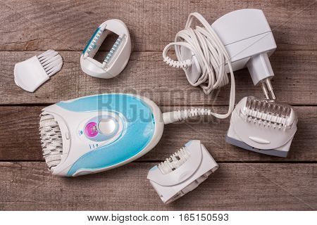 electric epilator on an old wooden background. Hair removal device
