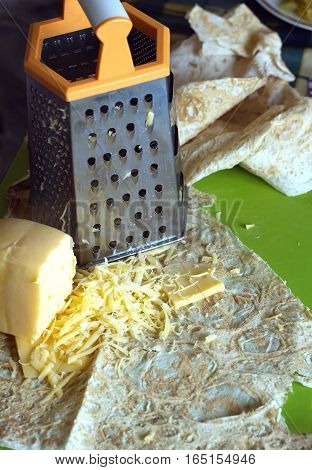 Cooking on kitchen desk. Grater, pita bread and sliced cheese. Vertical close-up photos