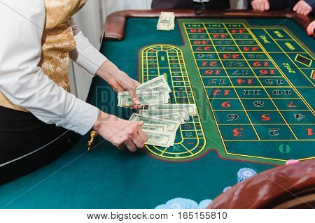 Croupier counts the money. Game of roulette. Table roulette