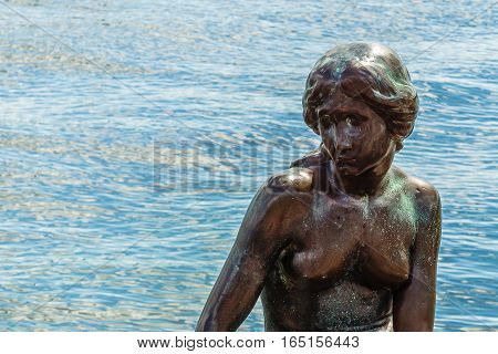 Copenhagen, Denmark, July 13, 2016 - Famous little mermaid sitting on a stone in the afternoon sunshine, against blue sea. The statue is the number one landmark in Copenhagen.
