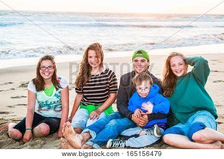 Beautiful Boys and Girls Sitting on Sandy Beach