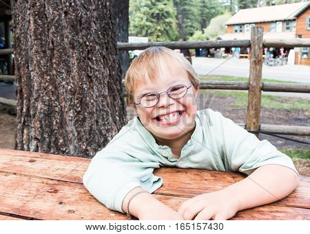 Happy Little Boy With Downs-Syndrome Sitting at Table