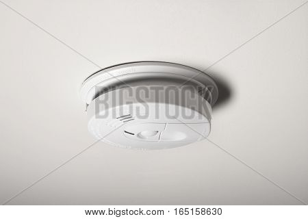 A smoke detector on the ceiling of a home.