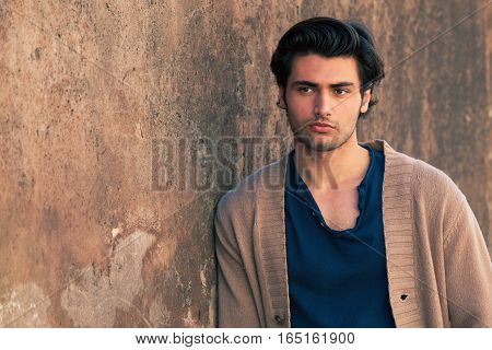 Engaging handsome man leaning against the wall. Stylish hair, beauty and attractive look.