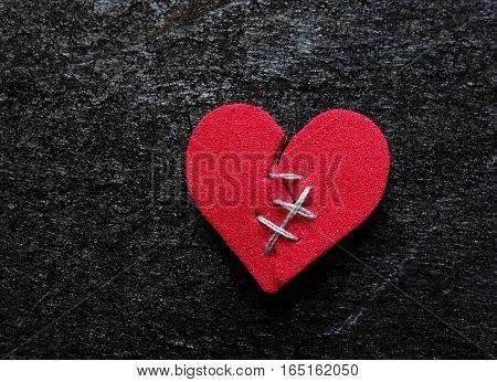 Red broken heart with thread stitches on dark background