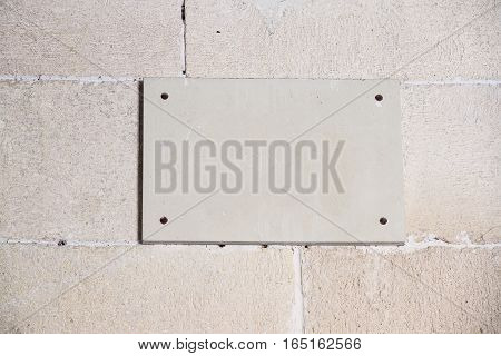 foreground of a empty plaque on a wall of stone
