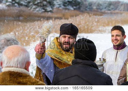 Rovzhi Ukraine - January 19 2014 Christian holiday Baptism in the Orthodox calendar. Father emotionally and abundantly sprinkles parishioners with holy water.