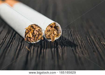 cigarette left on the brown wooden table close up with copy space