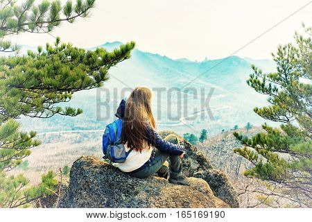 Young woman sitting on a rock with backpack and looking to the horizon.