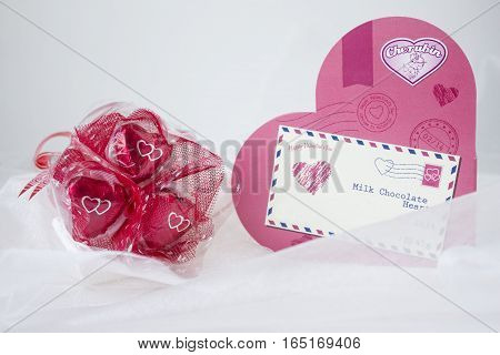 horizontal image of a cluster of valentine chocolates wrapped in red paper with a pink heart shaped box with an envelope  attached and text saying