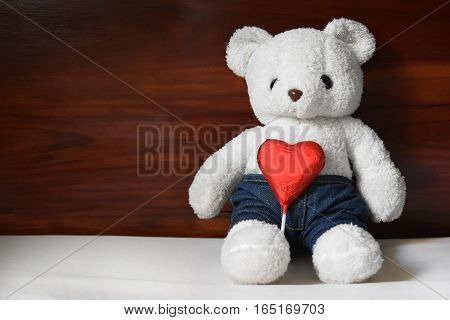 Dolly bears white and red heart on a white cloth The background is a brown wooden wall empty space for text.