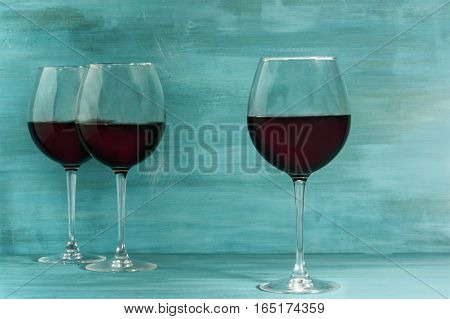 Glasses of red wine on a turquoise blue wooden background texture, with copy space. Selective focus