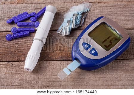 The blood glucose meter on an old wooden background .