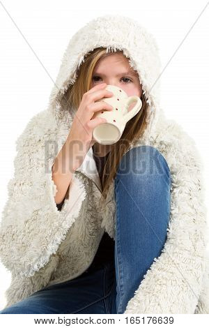 Young girl with blue jeans and winter jacket sitting holding cup isolated on white background