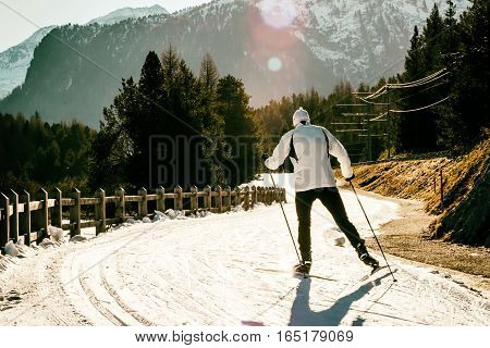 Back view of man in white jacket skiing on sunny day in mountains