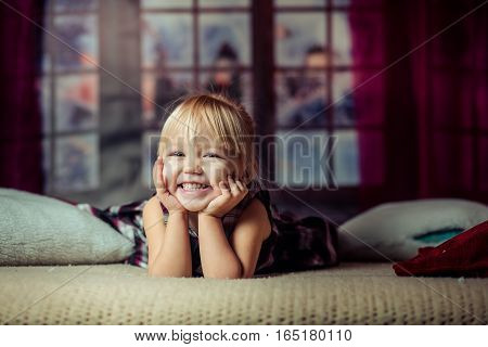 Portrait of cute girl lying barefoot in the bed