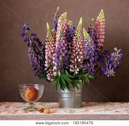 Still life with lupins and a peach in a vase on the table with a lace tablecloth in rustic style.