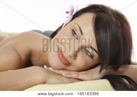 Young Woman Relaxing With Flower And Hot Stones