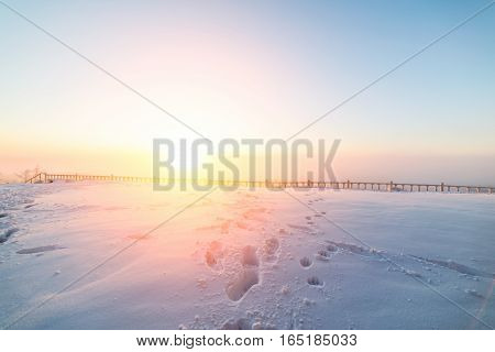 Sunny sunrise over the snowy plain. On the set of traces of snow. In the distance can be seen the architectural railing.