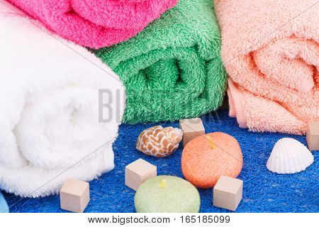 Colorful rolled towels with candles and shells closeup picture.