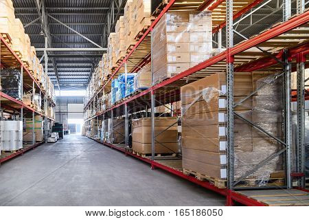 Large hangar warehouse industrial and logistics companies. Boxes and containers with goods placed on high shelves.
