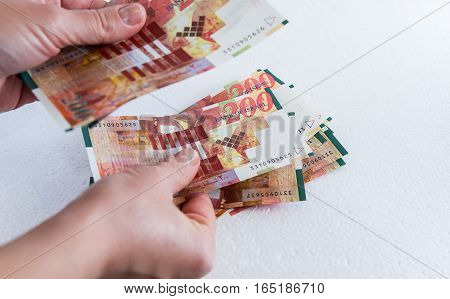 A female hand holding two hundred shekel bank notes against wood background. Concept photo of money banking currency and foreign exchange rates.