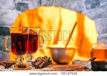 Mulled wine on the rustic table and pan in the oven