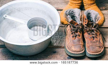 Feet wearing wool socks near winter fur boots and basin on the floor before footbath. Color toning