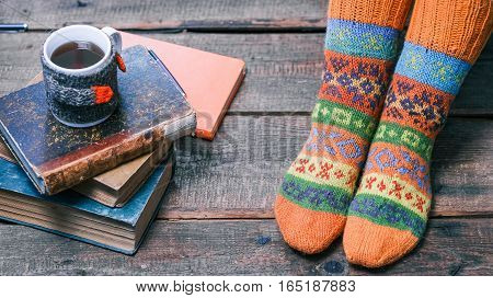 Female feet in warm winter socks on the wooden floor next to books stack and mug of tea