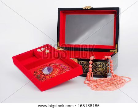 Picture of the opened jewel-box with red fit-out and amethyst pendant and pearl earring . Wooden jewel-box with pink coral bead necklace on white background. Side view.