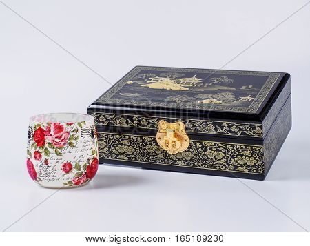 Picture of the wooden jewel-box with painting on wood and golden lock near decoupage glass on white background. Painted pattern on closed box for bijouterie. Side view.