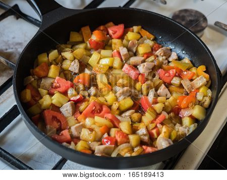 Picture of the frying colourful meal in the pan close up. Background of the colourful frying meal pattern close up. Black frying pan on a white gas stove.
