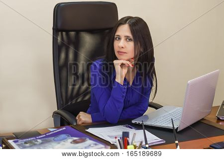 Young woman in office working on laptop