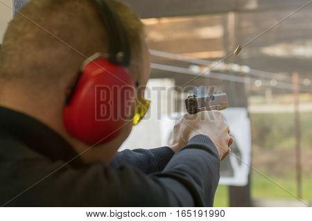 Shooting With A Pistol. Man Firing Pistol In Shooting Range.