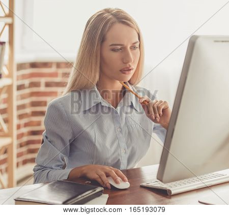 Beautiful pensive business lady in formal shirt is using a computer while working in the office