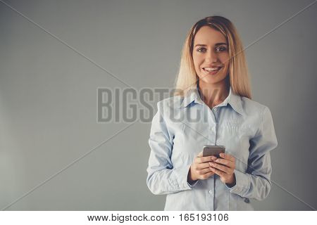 Beautiful business lady in formal shirt is using a smartphone looking at camera and smiling on gray background