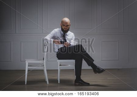 Man with a beard. Businessman thinking. Businessman sitting on two chairs. A guy in a business suit. Funny man with a beard