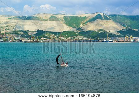 Sports sailboat and panorama of Novorossiysk commercial sea port