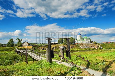 the bridge over the river Chusovaya leading to the temple on the rocky banks of the river Chusovaya on a summer day. Russia the Urals the village of Sloboda